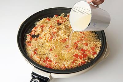 米をつややかにいため、トマトを混ぜたら、Aのスープを注ぎ入れる