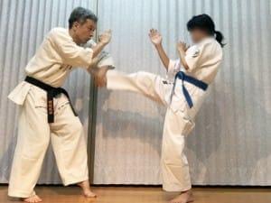 Aは右の前蹴りで攻撃。Bは少し下がって左手の下段払いで受け。