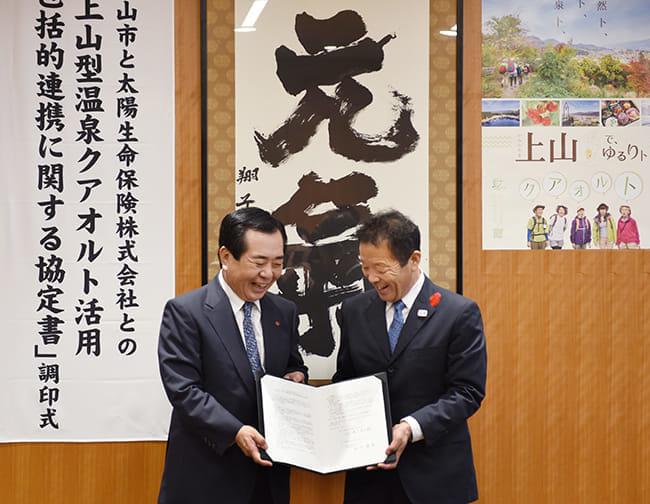 協定書にサインを交わした太陽生命の田中勝英社長(左)と、上山市の横戸長兵衛市長(3日、東 京都中央区の太陽生命本社で)