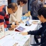 医療ネットワーク事務局のブースで、担当者の説明を受けながら血管年齢を測る人たち(2016年11月19日、東京都世田谷区の日本体育大学で)