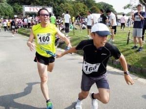 職場仲間の部で1位になった大濠公園リレーマラソンで次走者にたすきを渡す筆者(2011年10月)