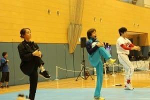 準備体操を実演する佐藤弘道さん(中央)と田中理恵さん(左)ら