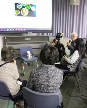 スクリーンに映った写真をもとに会話する「共想法」の実演(12月13日、千葉県柏市で)=山本淳一撮影