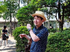 「平将門の首塚」の前で参加者に説明する泉さん