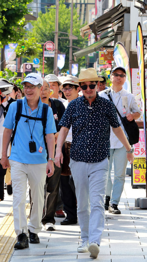 靖国通りの街並みを説明しながら参加者と一緒に歩く泉さん