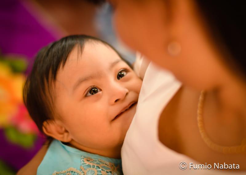 【名畑文巨のまなざし】赤ちゃんはダウン症。とても元気でかわいく、母親を見つめる一瞬のまなざしに、無条件の信頼感と、とても大きな生のエネルギー(生命力)を感じます。ミャンマーの旧首都ヤンゴン市にて。