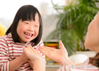 【名畑文巨のまなざし】  女の子はダウン症です。聴覚障害もあり、手話でコミュニケーションをとっています。天性の明るさがあって、小学校では、いつも周りに子どもたちが集まってくるのだとか。手話を知りたいと思ったり、いたわってあげたいという優しさが芽生えたり。ハンデのある子を離れて見るのではなく、自然と関わりたいという気持ちが湧いてきて、優しい空気が教室に広がっているのだそうです。京都府にて。