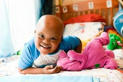【名畑文巨のまなざし】   7歳のダウン症のタペロくん、撮り始めからこんなテンションでした。おどけてばかりですが、全然憎めないタイプ。すぐに彼が好きになりました。それは、ファインダー越しに、「心がとても純粋なんだな」と一瞬で感じたからでしょう。その心に引き込まれていくように、夢中でシャッターを切っていました。南アフリカ共和国プレトリア市にて