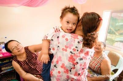 【名畑文巨のまなざし】ミャンマーの赤ちゃん(その1) ミャンマーでは、3世代ぐらいが同居する大家族が一般的です。1歳のAくんはダウン症。おばあちゃんや大おばあちゃんら、皆にかわいがられていて幸せそうでした。家族のカットが撮れたので、「次はご近所の方々と触れ合っているところを撮れませんか?」とお願いしてみました。「いいですよ」と快諾してくれて、おうちの前で撮ることになったのですが……。ミャンマー・ヤンゴン市にて(続く)