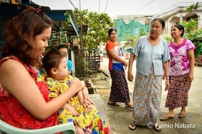 【名畑文巨のまなざし】ミャンマーの赤ちゃん(その2) お家の前で撮影、お母さんは心なしか緊張していました。そこにご近所さんが来ましたが、皆、けげんな顔…。「えっ……、ひょっとして初めて!?」。実は今まで、子どもにダウン症の障害があることは言っていなかったらしく、この時が初めての顔見せだったらしいのです。そうとは知らず、気軽にお願いしてしまったことを後悔しました。ミャンマー・ヤンゴン市にて(続く)