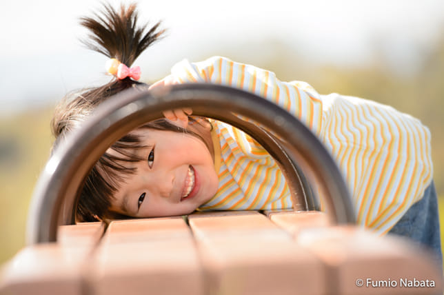広汎性発達障害のSちゃん(その3) それからはもう、「おじさん(私)大好きモード」です。表情が本当にキラキラと輝き始めます。そして撮影の合間に休憩していると、突然、つかつかとやってきて、ベンチに顔をうずめ、手すりの間からこんな笑顔を……。200%受け入れてくれた瞬間でした。京都府にて