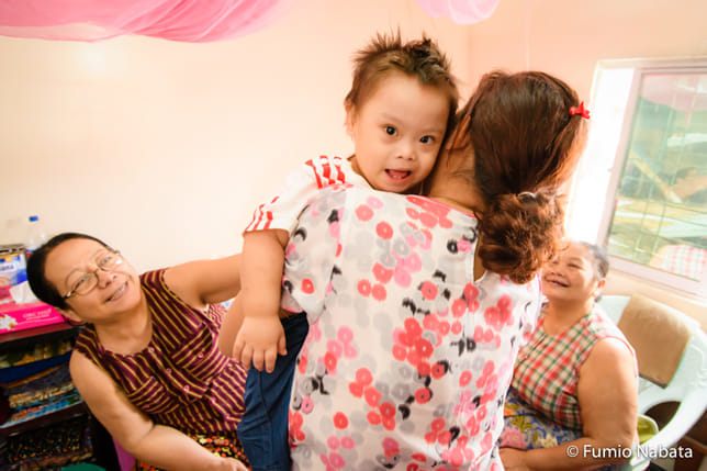 ミャンマーの赤ちゃん(その1) ミャンマーでは、3世代ぐらいが同居する大家族が一般的です。1歳のAくんはダウン症。おばあちゃんや大おばあちゃんら、皆にかわいがられていて幸せそうでした。家族のカットが撮れたので、「次はご近所の方々と触れ合っているところを撮れませんか?」とお願いしてみました。「いいですよ」と快諾してくれて、おうちの前で撮ることになったのですが……。ミャンマー・ヤンゴン市にて(続く)