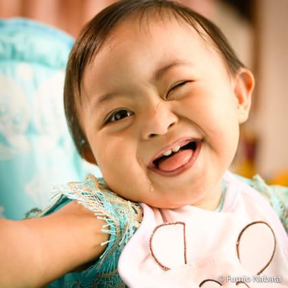 ポジティブエナジーズ(その3) 世界をめぐって撮影したダウン症の子どもたちは、みなポジティブなエネルギーにあふれていました。ミャンマーの1歳の赤ちゃん、とてもかわいい。それに、かなりお 転婆てんば です。めまぐるしく変わる表情は、どれも生き生きとしていて、三世代が同居する大家族の皆を笑顔にしていました。ミャンマー・ヤンゴン市にて