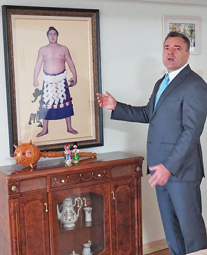 「このパネルは大鵬関からもらったんですよ」と説明するユーリ・ルトビノフさん(東京都港区のウクライナ大使館で)