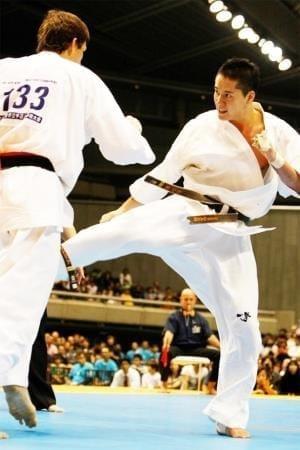 外国の強豪にローキック(下段回し蹴り)を入れる選手時代の赤石さん。上の2枚の写真とは違って、鬼気迫る表情だ(2011年11月、第10回世界大会で。赤石さん提供)