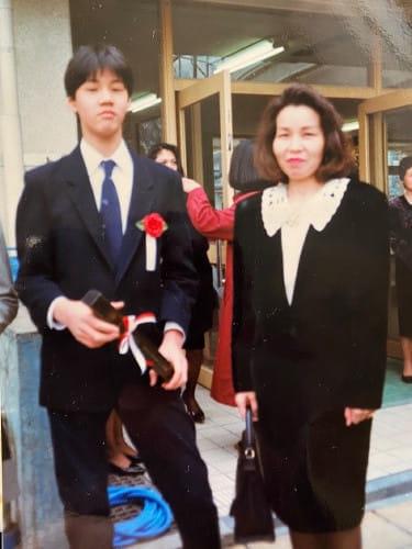 小学校の卒業式で母親と。12歳。幼いころから身長が高く、いつもクラスで席はいちばん後ろだったという(ともに赤石さん提供)