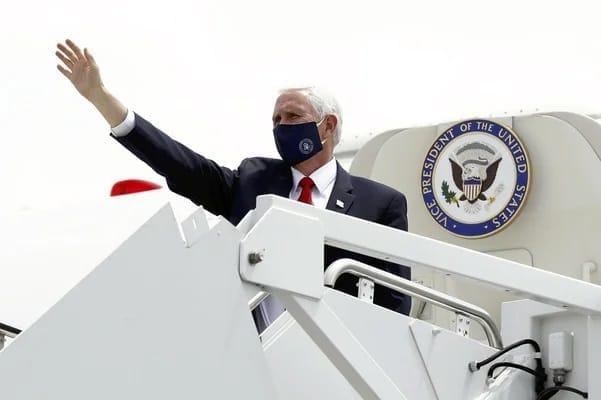 28日、米南部テキサス州を離れる際、マスク姿で手を振るペンス副大統領(AP)