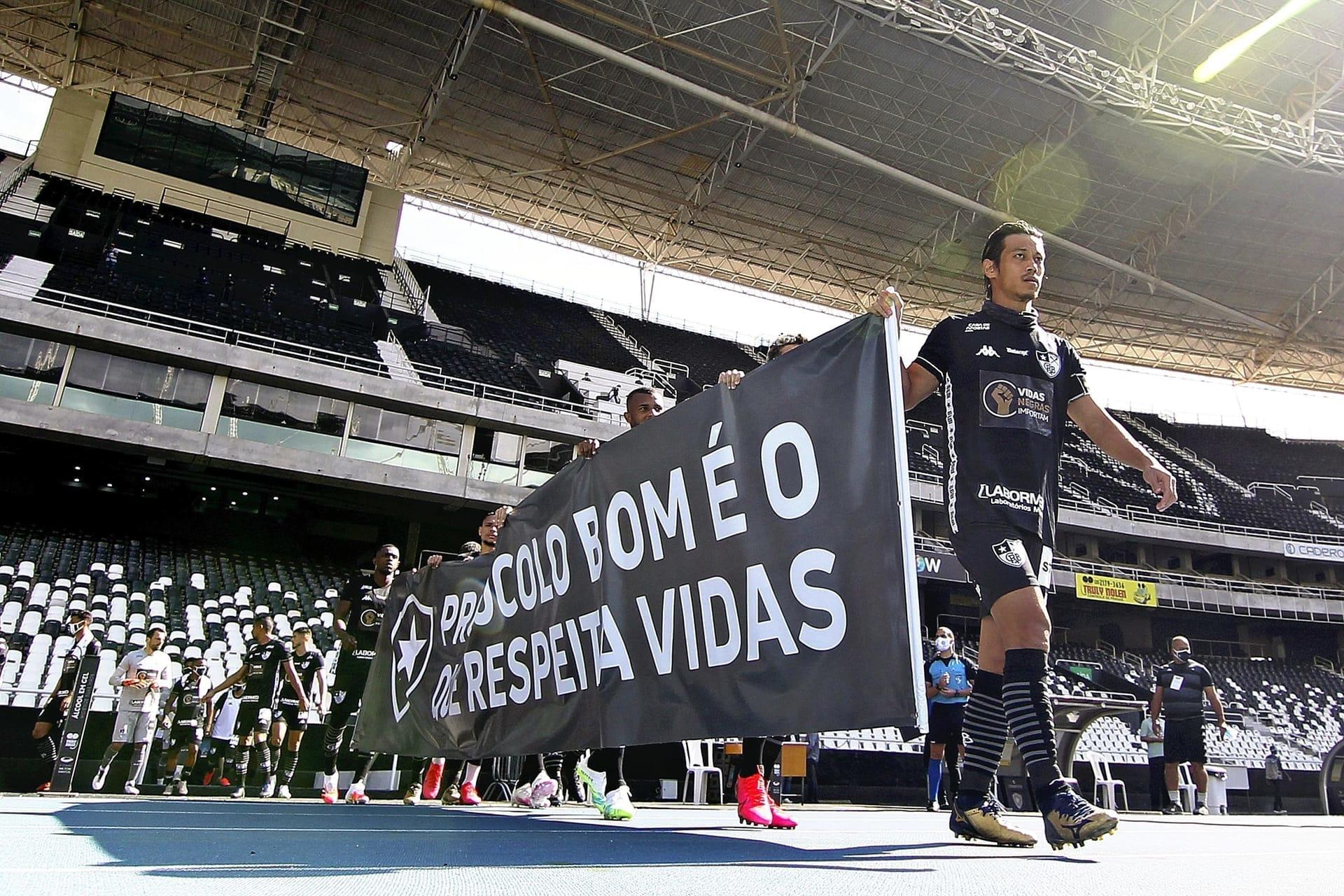 28日、リオデジャネイロのサッカースタジアムで、「人命を尊重して」と書かれた横断幕を持って歩くボタフォゴの本田圭佑選手(右)ら=Vitor SILVA、ボタフォゴ、AFP時事