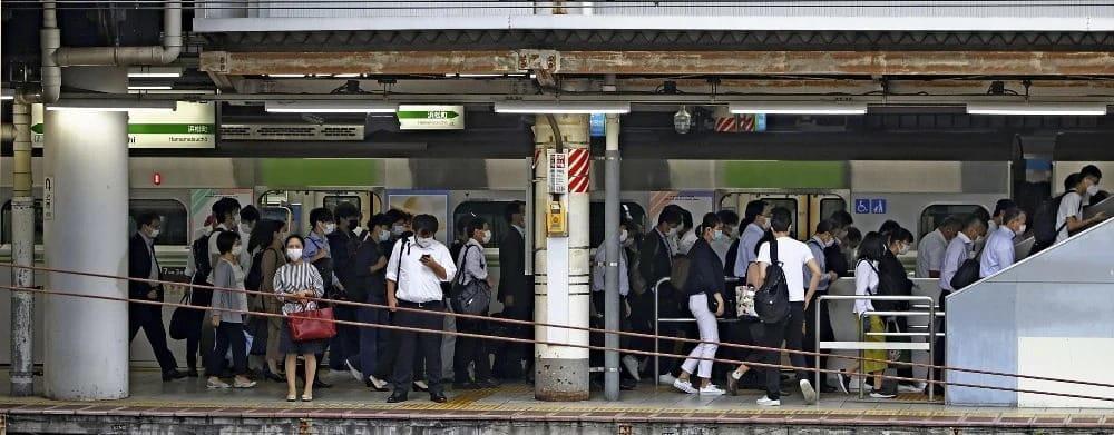 緊急事態宣言が解除された後、マスク姿のサラリーマンらで混雑するJR山手線の通勤電車(今年6月、東京・田町駅で)