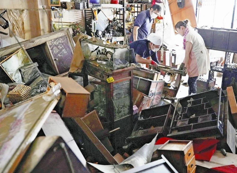 人吉市内で、商品や家財が散乱した店内を片付ける人たち