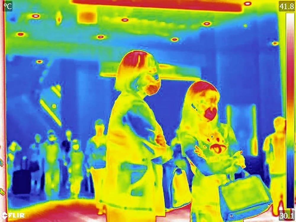 (上)温度の違いを色で表すサーモグラフィーカメラでJR大阪駅前を行き交う人々の姿を撮影した。2人の女性のマスク部分は赤く、他の部分より温度が高い(青は温度が低く、緑、黄、赤、白の順番で温度が高くなる)(2日午後4時18分、大阪市北区で)=浜井孝幸撮影(下)強い日差しの中、マスク姿で歩く人たち(5日、大阪市北区で)