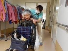 ホームの廊下を車椅子を押して歩くリハビリ中の渡辺さん