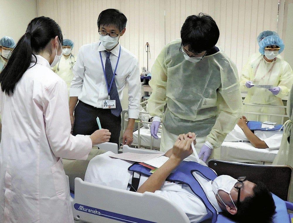 感染防御ガウンなどを着用して患者役の症状を確認する職員ら