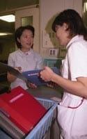 カウンセリングした患者について看護師に報告する岡本さん(左)