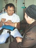 B子さんに体調を聞きながら点滴の準備をする腫瘍内科医の横山さん(川口市立医療センターで)
