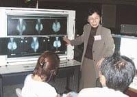 マンモグラフィ画像の見方について医師に講義する放射線科医