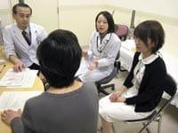 遺伝子検査を受ける前に、(奥左から)大住さん、遺伝カウンセラーの増田さんらからカウンセリングを受ける女性(手前)(四国がんセンターで)