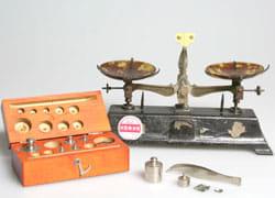 調剤天秤  昭和初期昭和62年の検査合格証を受けている。昭和初期から50年余り薬局で使用されていた。(秤量200 g 感量0.2g 組分銅0.1 g ~ 100 g)