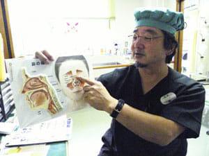 「超低周波音の微細な振動が体内の空洞を振るわせ、体調不良が起こる可能性がある」と説明する医師の有吉靖さん(宇久島の宇久診療所で)