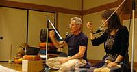 レーズンを手に説明するカバットジン博士。右は通訳の女性(横浜市の総持寺で。マインドフルネスフォーラム2012実行委員会提供)
