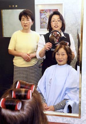 美容師の柳大路さんから髪のセットに関するアドバイスを受ける、海江田さん(右下)と沼田さん(左)(大阪市北区で)
