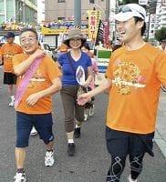 支援者や家族に囲まれ、タスキをつないだ松浦さん(手前左)=東京都町田市で