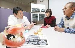 馬場さん(左)からインプラントの説明を受ける(右から)打谷さんと中野さん(大阪市中央区で)