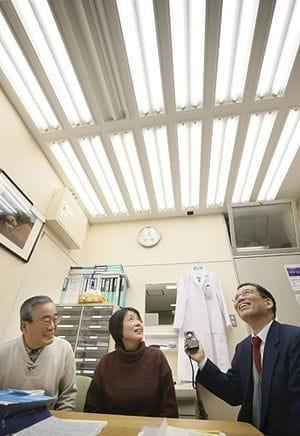 「陽光はこの何倍も明るい。昼間に屋外で体を動かすことで、夜はいい眠りができます」。特別仕様の蛍光灯を備えた研究室で、宮崎さん(右)から説明を受ける森本さん夫妻(2月25日、大津市の滋賀医大で)
