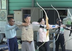 講師の岡部さん(左端)にフォームの指導を受け、小泉さん(左から2人目)と高橋さん(左から3人目)が的を狙う(堺市西区の浜寺公園アーチェリー練習場で)=長沖真未撮影