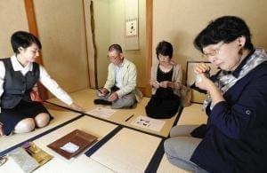 安里さん(左)の指導で香りを聞く畑山さん(右)と中村さん夫妻(京都市上京区で)=宇那木健一撮影