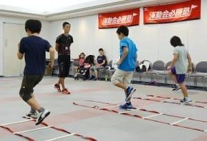はしご形のひもの上を決められたパターンで走り抜ける練習に取り組む小学生(撮影・秋元和夫)